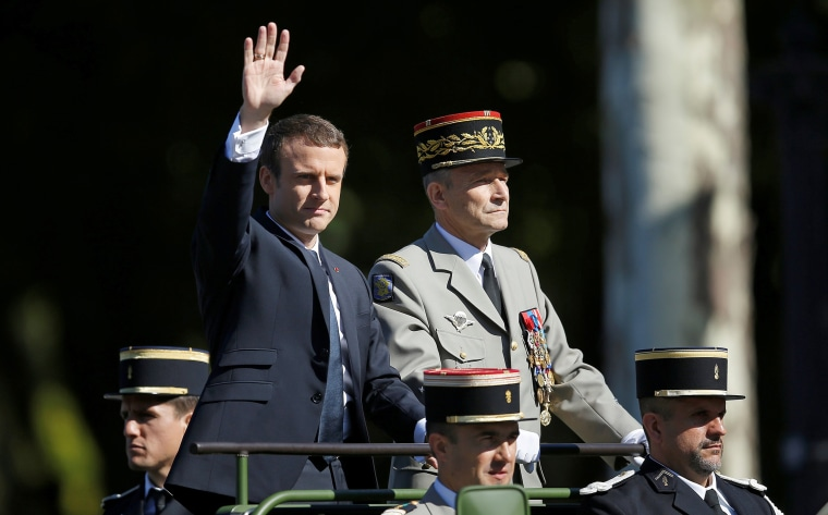 French President Emmanuel Macron and French Army Gen. Pierre de Villiers arrive in a command car for the traditional Bastille Day military parade on the Champs-Elysees in Paris on July 14, 2017.
