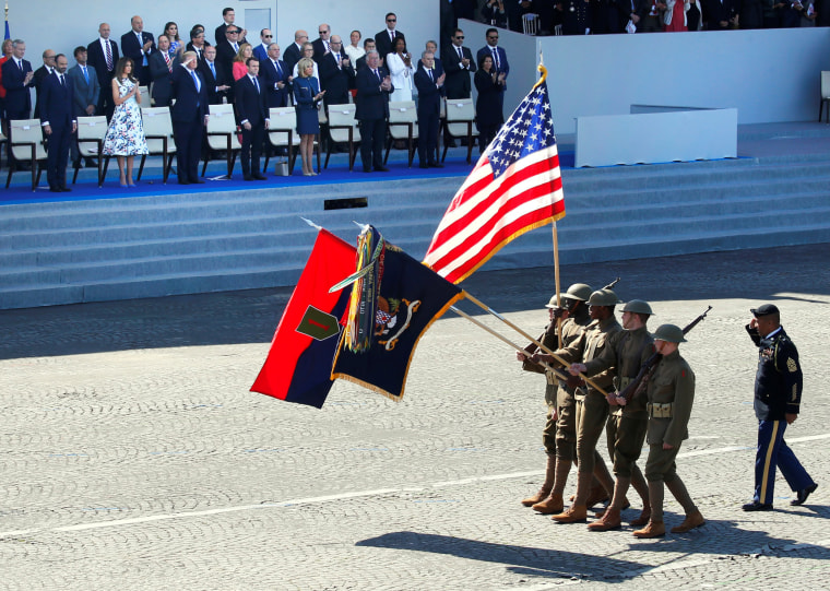 U.S. soldiers wearing World War I helmets march past Macron, his wife Brigitte Macron, President Trump and first lady Melania Trump. 