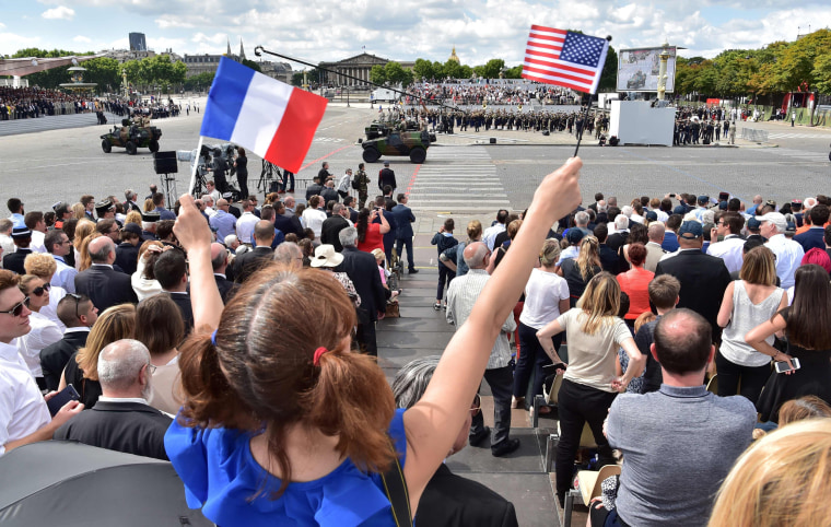 A girl waves the French and US flag during the annual Bastille Day military parade on the Champs-Elysees avenue in Paris on July 14, 2017.
