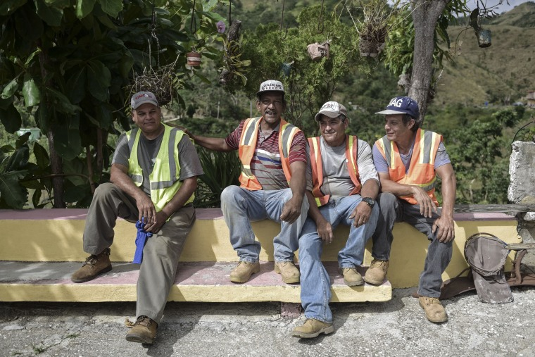 Local residents, who are also municipal workers in the town of Coamo, rest after restoring power to a house.