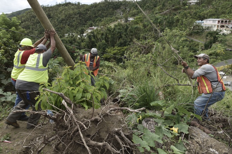 Local residents, who are also municipal employees, work to restore power in the town of Coamo.