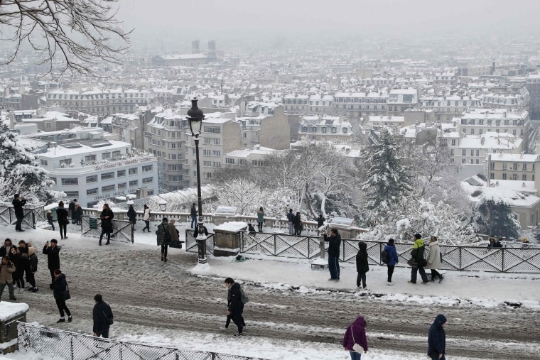 People walk on the snow-covered Montmartre hill in Paris on Feb. 7, 2018. Heavy snowfall caused major travel disruptions in the northern half of France and in Paris after the weather conditions caught authorities off guard.