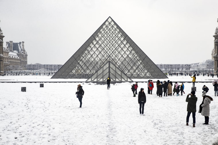 Tourists take photos outside the Louvre on Feb. 7.