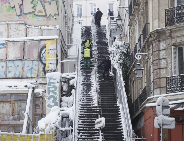 City employees clear snow from a staircase in Montmartre on Feb. 7.