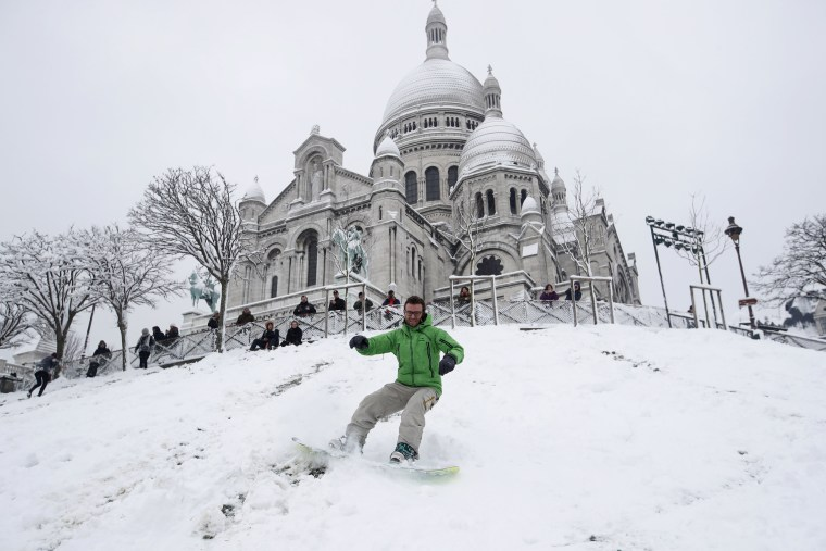 A snowboarder goes down Montmartre hill in front of the Sacre Coeur Basilica on Feb. 7.