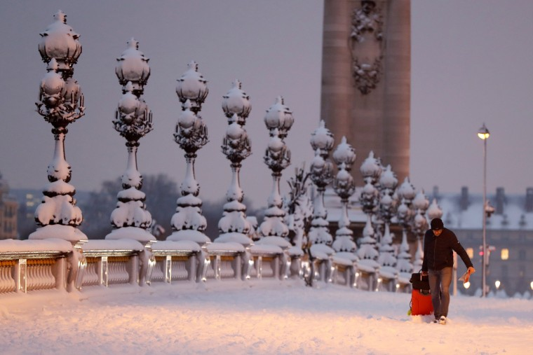 A man drags a suitcase along the Pont Alexandre III bridge during the early morning in Paris on Feb. 7.