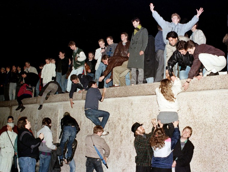Image: People climb the Berlin wall at the Brandenburg gate