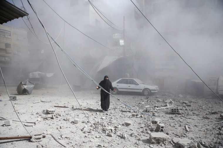 A woman walks on the rubble of damaged buildings after an airstrike in the rebel-held Eastern Ghouta town of Douma near Damascus, Syria on Feb. 7, 2018.