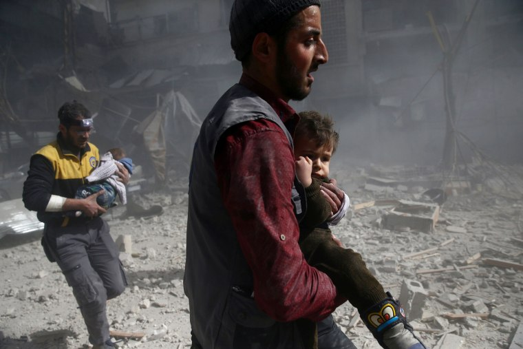 Men carry small children in their arms in Douma on Feb. 7.