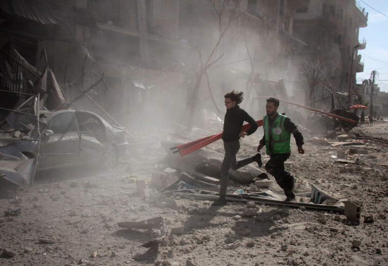 People run in the rubble of buildings to rescue victims in Douma on Feb. 7.