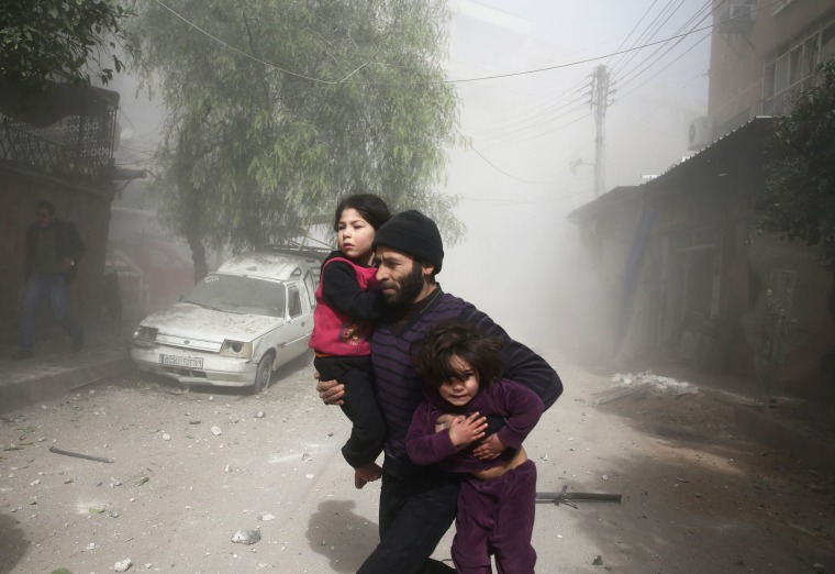 A man carries children through dust in Douma on Feb. 7.