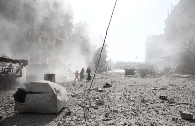 People walk on the rubble of damaged buildings in Douma on Feb. 7.