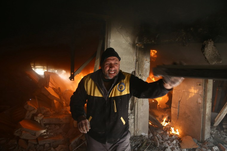 A man throws an object as a fire burns behind him in Douma on Feb. 7.