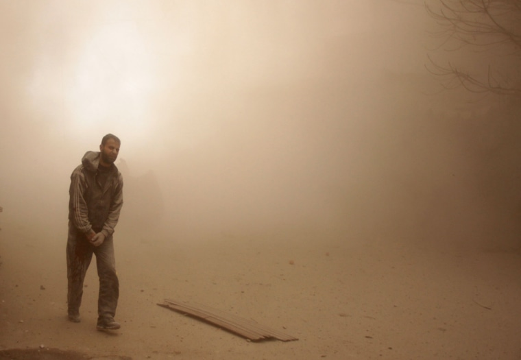 A man walks through smoke and dust in Douma on Feb. 7.