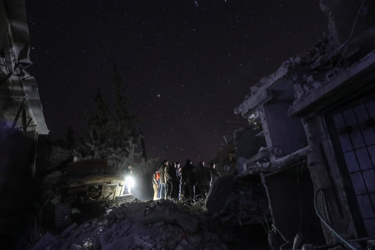 Civilians use their mobile phone as flashlights while helping look for the remains of missing people stuck under rubble for more than five hours in Douma on Feb. 6.