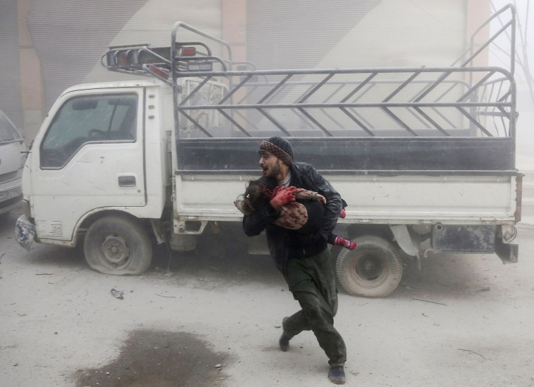 A man carries a child in Saqba, in Eastern Ghouta on Feb. 6.