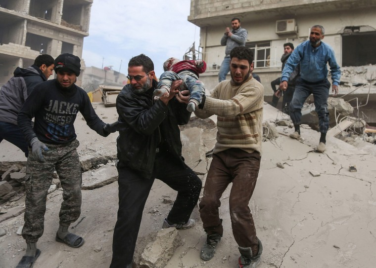 A man hands over a child to his father after being rescued from beneath the ruins of a building that collapsed following reported Syrian air force strikes in the rebel-held town of Saqba, in the besieged Eastern Ghouta region on the outskirts of the capital Damascus, on Feb. 6, 2018.