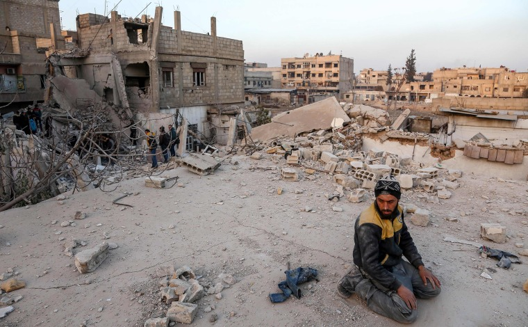 A Syrian Civil Defence volunteer performs ritual sunset prayers next to a collapsed building in Arbin, in Eastern Ghouta on Feb. 6.