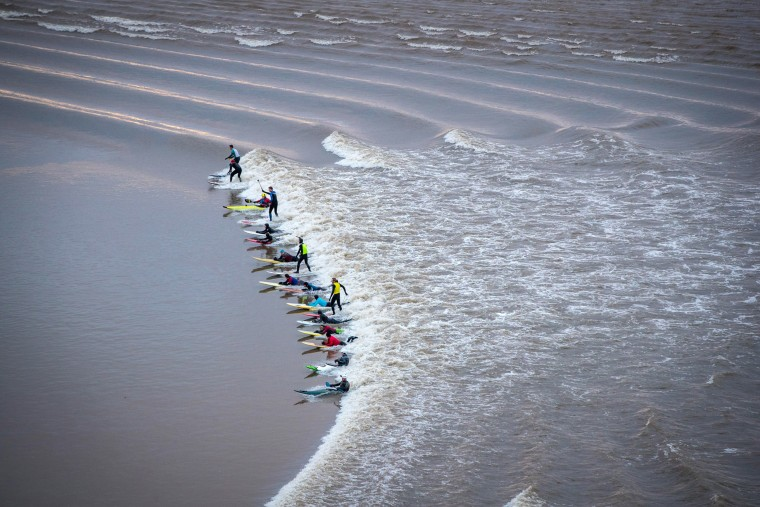 urfers attempt to ride the Severn Bore as it passes through Newnham on Severn, England, on Feb. 2, in Gloucestershire, England. The bore will likely be one of the largest of the year following this week's supermoon. The natural tidal phenomenon pushes a 4-foot wave up the Severn Estuary and is most dramatic in the spring when the tides are at their highest.