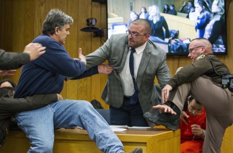 Randall Margraves, the father of three girls who say they were molested by Larry Nassar, lunges at the former gymnastics doctor in Eaton County Circuit Court in Charlotte, Michigan, on Feb. 2. The chaos that erupted in the Michigan courtroom highlighted the high emotions that have marked three weeks of hearings for Nassar, who has pleaded guilty to abusing 10 girls but is accused by more than 250 others. Margraves, 58, later apologized for the outburst, and the judge let him go without any punishment or charges.