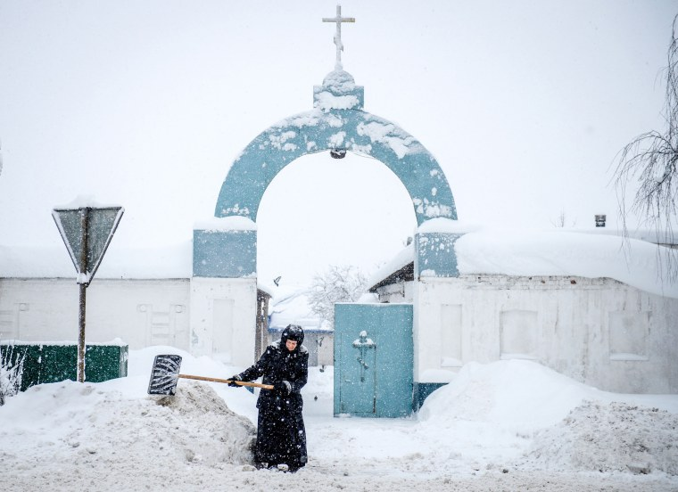 A nun removes snow outside a convent in the village of Bogoslovo, Russia, on Feb. 4.