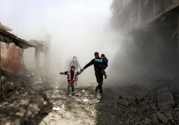 Civlians flee following airstrikes in the rebel-held town of Jisreen, Syria, on Feb. 8. The besieged eastern Ghouta region in the suburbs of Damascus has been bombarded for days leaving scores dead and hundreds wounded. The Britain-based Syrian Observatory for Human Rights said 211 people have been killed in eastern Ghouta since Monday. 