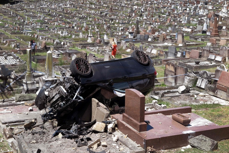 A Mercedes SUV lies surrounded by gravestones at a cemetery in the Sydney suburb of South Coogee on Feb. 6. The early morning crash caused significant damage after the driver failed to take a corner, crashing through a wall before landing on the gravestones. Police said the driver failed a roadside alcohol breath test before going to hospital.