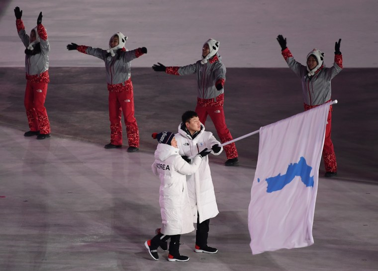North Korean ice hockey player Hwang Chung Gum and South Korean bobsledder Won Yun-jong, right, wave a Korean unification flag as they lead the Korean delegation.