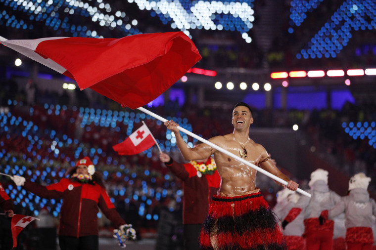 Pita Taufatofua carries the flag of Tonga.