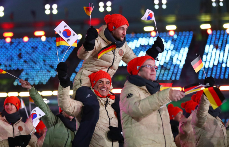 The German delegation waves South Korean and German flags.