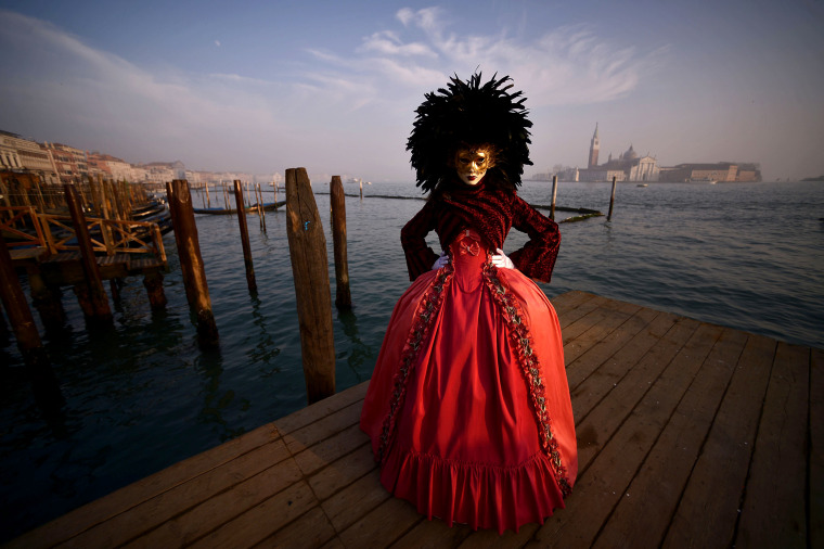A masked reveller wearing a traditional carnival costume poses in St Mark Square during Venice's Carnival on Jan. 28, 2018.