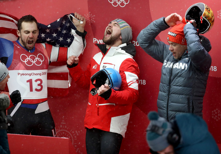 Chris Mazdzer (silver) of the U.S., David Gleirscher (gold) of Austria and Johannes Ludwig (bronze) of Germany celebrate following the luge men's singles competition on Feb. 11.