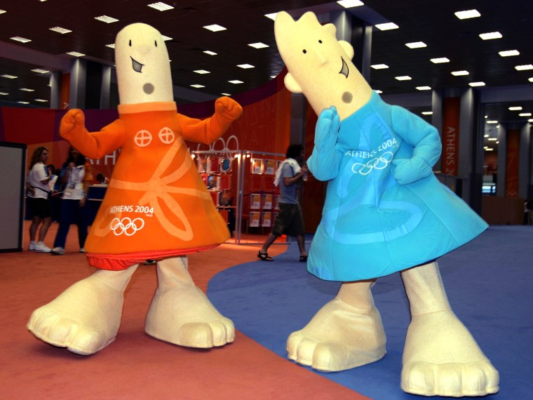The Offical Mascots of the Athens 2004 Olympic Summer Games Athena (L) and Phevos (R) walk through the lobby of the Main Press Center (MPC) prior to the start of games August 10, 2004 in Athens, Greece. The games kickoff with the Opening Ceremonies on August 13.