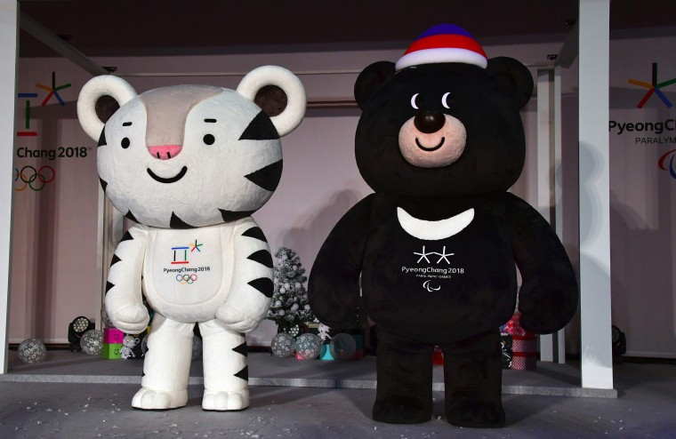 """Mascots for South Korea's 2018 Pyeongchang Winter Olympics, a white tiger named """"Soohorang"""" (L) and an Asiatic black bear named """"Bandabi"""" (R), stand on a stage during the mascots' first public staging event at Hoenggye elementary school in Pyeongchang, about 150 kms east of Seoul, on July  18, 2016."""