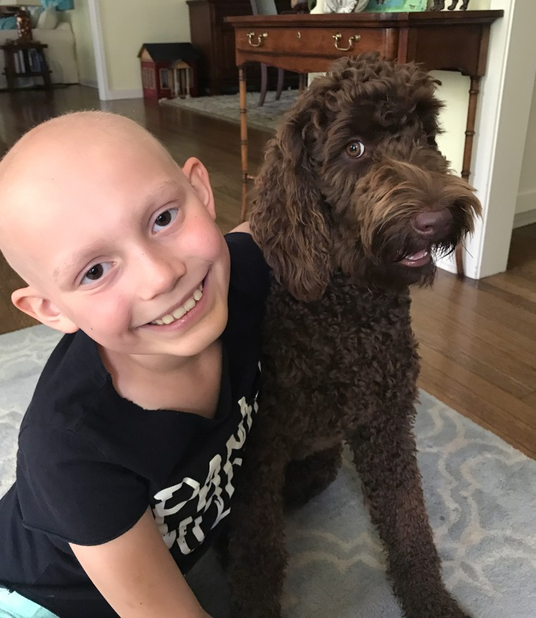 While she's feel bad after chemotherapy treatments, Riley likes hanging out with the family dog.