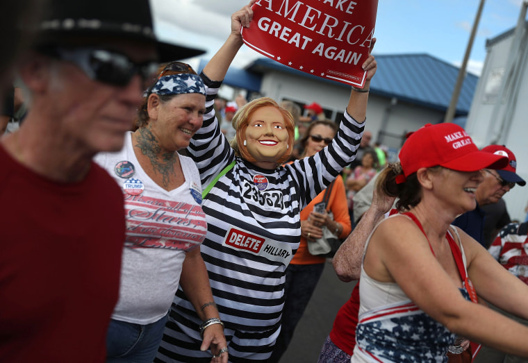 Image: A supporter of Republican presidential candidate Donald Trump wears anti-Hillary Clinton prison garb