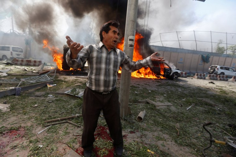 Image: An Afghan man reacts at the site of a blast in Kabul, Afghanistan