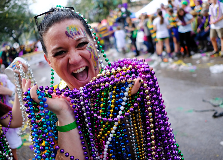 Karen Price shows off her catch of beads from the The Krewe of Thoth parade during Mardi Gras celebrations in New Orleans on Feb. 11, 2018.