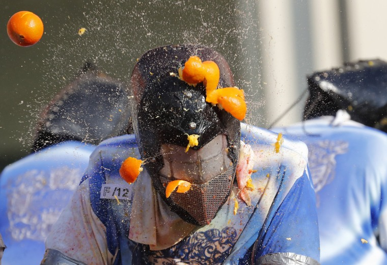 A person wearing a protection helmet is pelted with oranges during Carnival celebrations in Ivrea, Italy on Feb. 12, 2018.