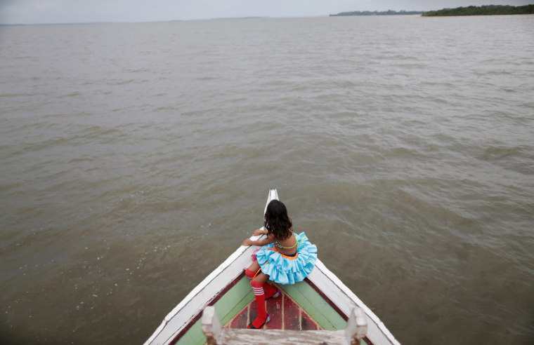 "A member of the ""Bloco Real Folia"" group sits in front of a boat during Carnival of the Waters where colorful boats navigate the Jaituba river around the islands near the city of Cameta, Brazil on Feb. 9, 2018."