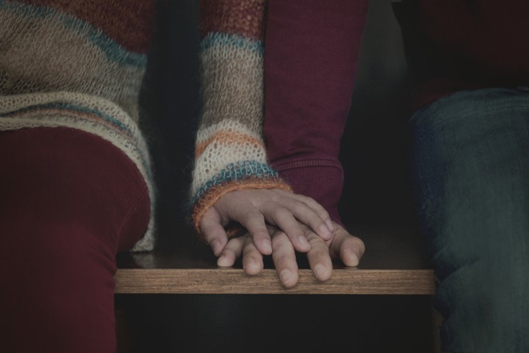 Image: A couple holds hands