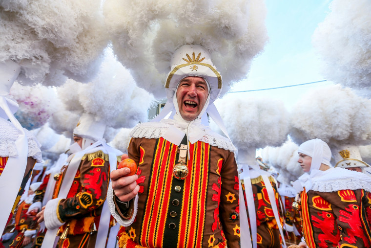 "Image: Festival participant known as ""Gilles"" throw oranges during Carnival celebrations in the streets of Binche"