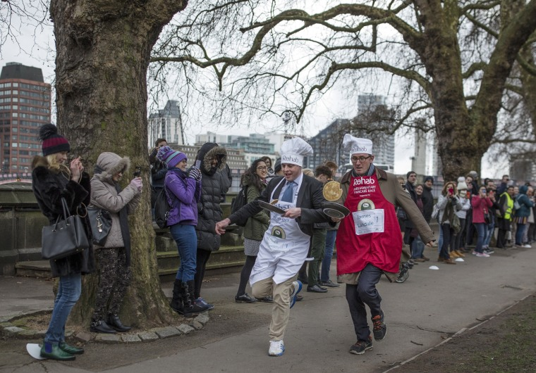 Image: The BBC's Diplomatic correspondent James Landale, right, and MP Matt Warman approach the first corner in the annual Parliamentary Pancake Race