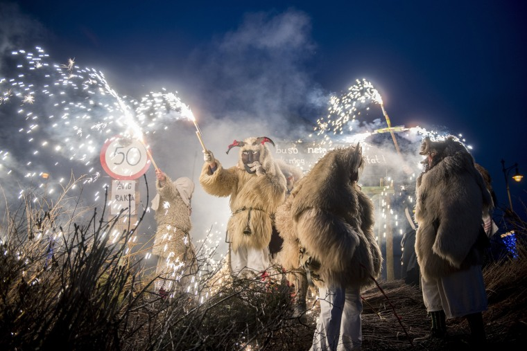 Image: Revelers wearing sheepfur costumes light a bonfire to burn a coffin, symbolizing winter