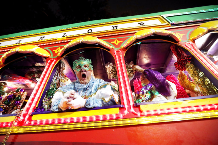 Image: Float riders encourage the crowd as the Krewe of Orpheus rolls through New Orleans
