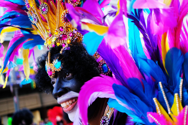 Image: A foot marcher with the Krewe of Zulu makes his way down the street on Fat Tuesday