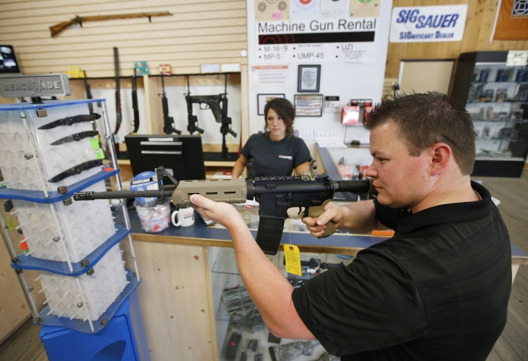 Image: An employee shows an AR-15 rifle to a customer