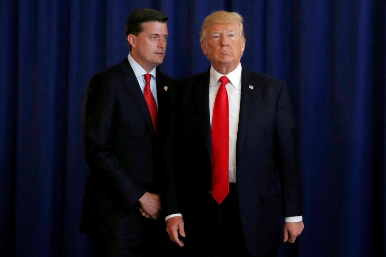 Image: White House Staff Secretary Rob Porter reminds U.S. President Donald Trump he had a bill to sign after he departed quickly following remarks at his golf estate in Bedminster, New Jersey on Aug. 12, 2017.