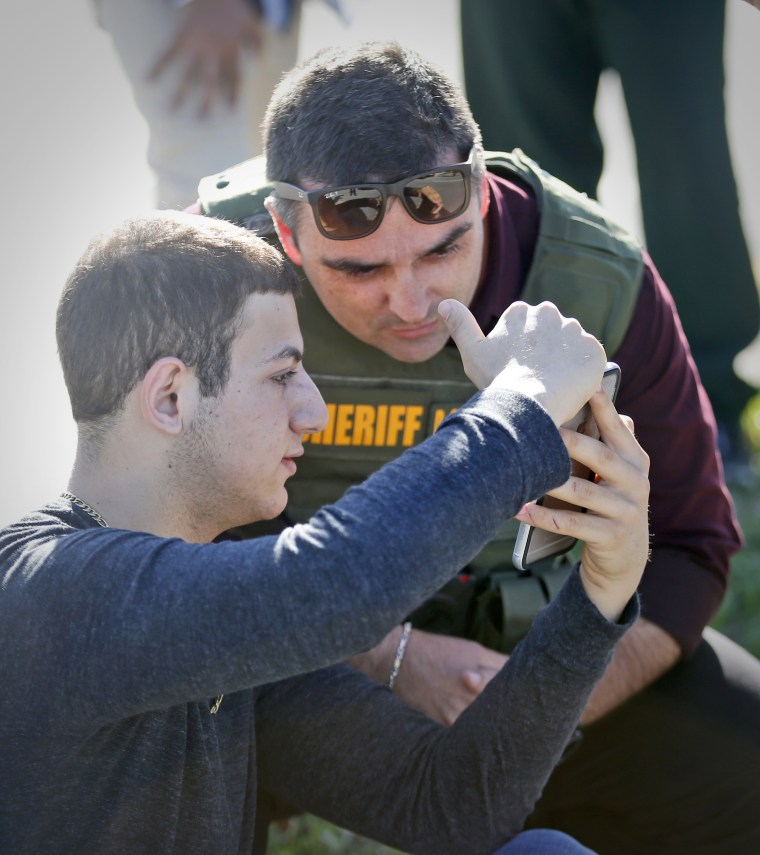 Image: A student shows a law enforcement officer a photo or video from his phone, on Feb. 14, 2018, in Parkland, Florida.