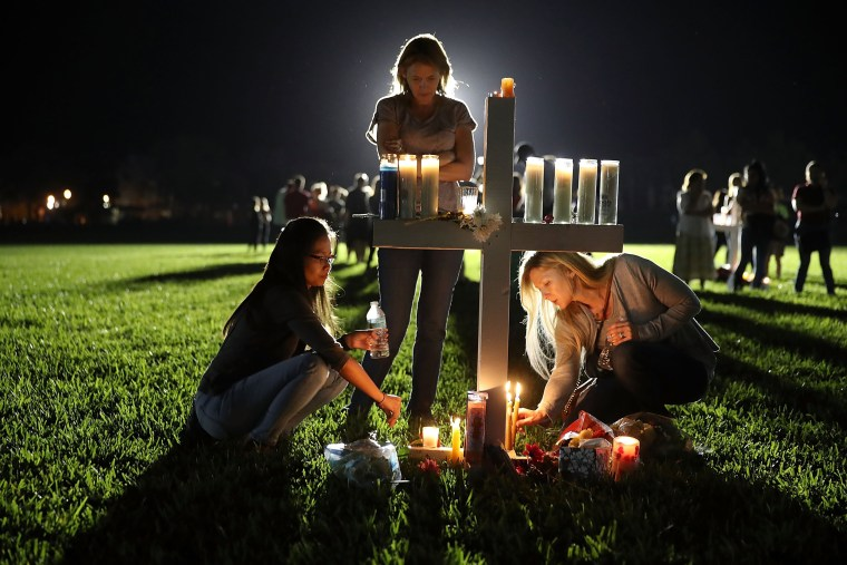 Maria Reyes, Stacy Buehler and Tiffany Goldberg light candles around a cross, as they attend a candlelight memorial service for the victims of the shooting at Marjory Stoneman Douglas High School that killed 17 people, on Feb. 15 in Parkland, Florida.